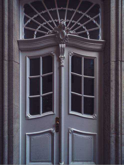 Double doors with intricate details on the transom and trim make this door way special. Historical details, antique details, marble door jamb, amid home, doors with glass inserts