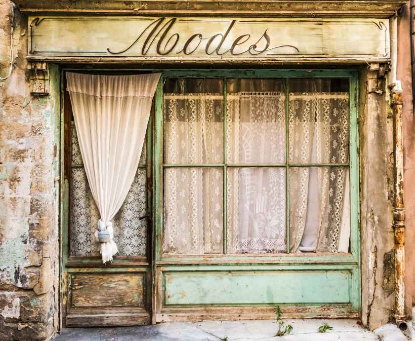 Oh how I would love to set up shop in a pretty storefront like this. She is a little weathered, but her details are beautiful! amid home, chippy paint, crochet, vintage lace curtains, rustic, old world, Modes Fashion, front doors with glass inserts